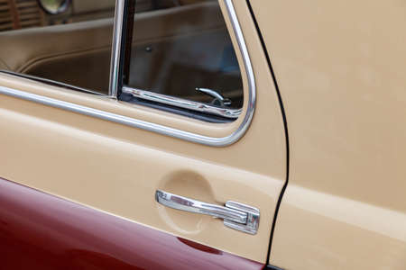 View on closed rear door with handle and corner wondow of the old Russian retro vintage car of the executive class released in the Soviet union in beige and brown. Auto service industry.