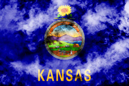 The national flag of the US state Kansas in against a gray smoke on the day of independence in different colors of blue red and yellow. Political and religious disputes, customs and delivery.