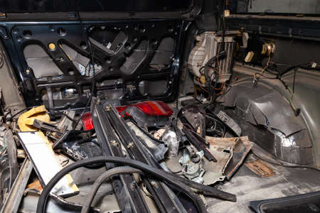 Car interior in the back of a van with a disassembled lining, seats removed, spare parts lying on the floor glass and rubber seal during preparation in a vehicle repair workshop. Auto service industry Imagens