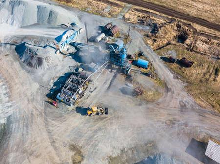 Vue aérienne d'une petite usine de production et de nettoyage des gravats et du ciment à proximité des tas de matériaux de construction du tuyau d'où part la fumée grise, le tracteur transporte le produit fini.