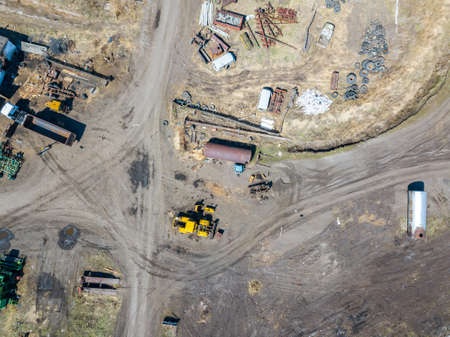 Aerial view of an excavator and yellow tractor transporting crushed stone, cement and sand during the extraction of minerals from the earth for the construction of roads and buildings on a sunny day. Reklamní fotografie