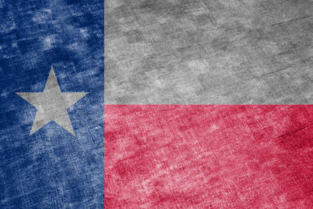The national flag of the US state Texas in against a gray textile rag on the day of independence in different colors of blue red and yellow. Political and religious disputes, customs and delivery.