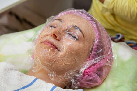 A young girl is lying on a couch during cosmetic procedures with a mask on the faces above which the beautician imposes a transparent film. Cleansing the face.