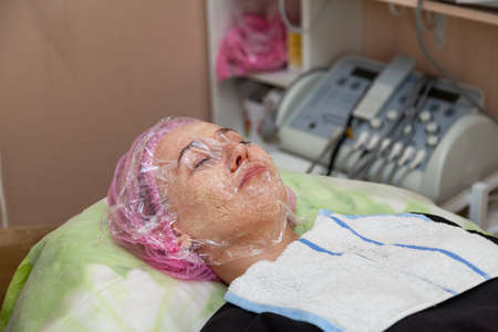 A young girl is lying on a couch during cosmetic procedures with a mask on the faces above which the beautician imposes a transparent film in the background technique for procedure. Cleansing the face Foto de archivo