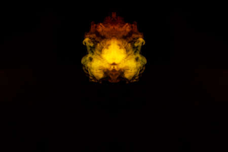 Abstract image of smoke of different green, yellow, orange and red colors in the form of horror in the shape of the head, face and eye on a black isolated background. Soul and ghost in mystical symbol