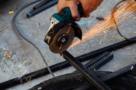 Close-up view strong man master without gloves on arms, performs metal cutting with an angle grinder in the garage workshop, blue and orange sparks fly to the sides