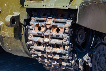 Close-up on a rusty old caterpillar of a green tank worn on wheels standing on the road. Military equipment for the murder and the achievement of peace between states. Tracks armored vehicles.