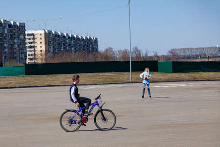Leninsk Kuznetsk, Russia - 05.03.2019: Rest in the park in the summer where teen ride bicycle without hands on steering on a clear sunny spring or summer day. Active outdoor recreation in the city.