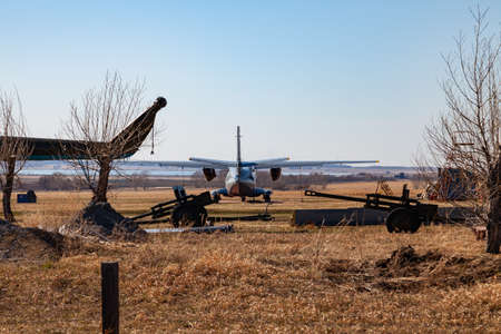 A small aircraft for the transport of passengers and paratroopers is behind the fence among the rarities of artillery guns and cannons in a field of yellow grass on the runway. Transportation of drugs