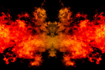 Smoke of different orange and red colors in the form of horror in the shape of the head, face and eye with wings on a black isolated background. Soul and ghost in mystical symbol