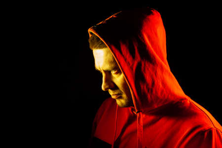 Close-up of the head of a man in an orange hood on the side of the side and looking forward with a yellow backlight. Feelings before battle, confrontation with a thoughtful look.