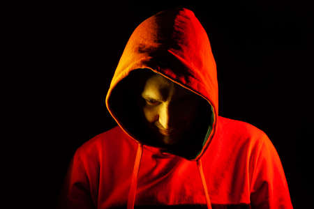 An adult man looks out from under the hood with a grin like a psycho or a maniac in an orange hooded sweatshirt highlighted in red and yellow on the sides on a black isolated background.