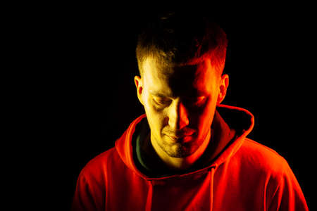 An adult guy stands with his head tilted and look down in an orange hooded sweatshirt highlighted in red and yellow on the sides with a pensive and regretful view on a black isolated background.