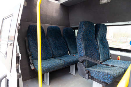 Five seats of a utility car in the back of a van with a partition dividing the salon into two parts, carpeted with a window and a hatch. Additional equipment of vehicles