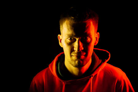 An adult man stands look forward in an orange hooded sweatshirt highlighted in red and yellow on the sides with angry view on a black isolated background.