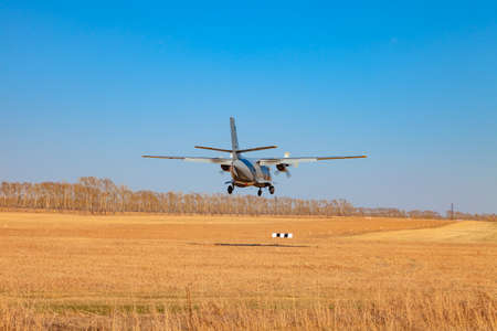 A small aircraft for the transport of passengers and paratroopers lands in a field on a landing strip with grass under a blue sky above the trees on a clear cloudless day. Air patrol.