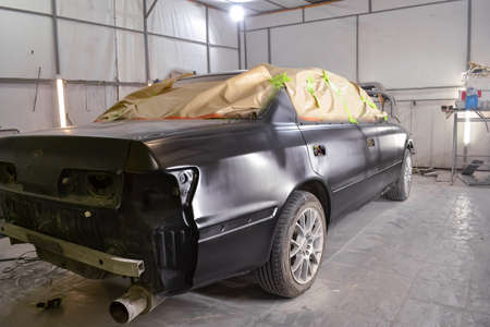 A sedan black car with windows covered in paper and adhesive tape to protect interior against splash during painting and repair after an accident in a workshop for body repair of vehicles