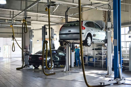 Two used cars with an open hood raised on a lift for repairing the chassis and engine in a vehicle repair shop. Auto service industry. 写真素材