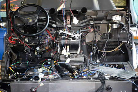 A lot of ravel multicolored wires from the car wiring lies in the cabin of dismantled car with connectors and plugs, a view through the window inside the battered car. Auto service industry