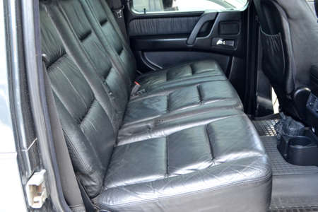 Clean after washing the rear passenger seats of matte black genuine leather inside the interior of an expensive suv, preparation before selling the car. Auto service industry. detailing cleaning.