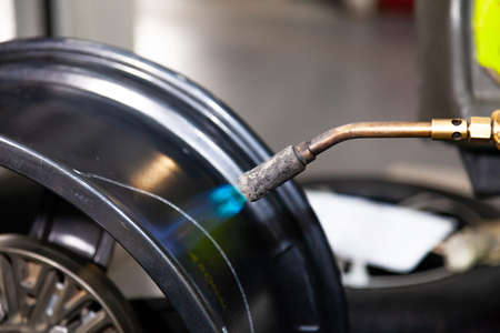 The process of repairing an automobile wheel using a special press on a machine for straightening disks for vehicles after damage in a pit on the road in the workshop with heating by flame of burner.
