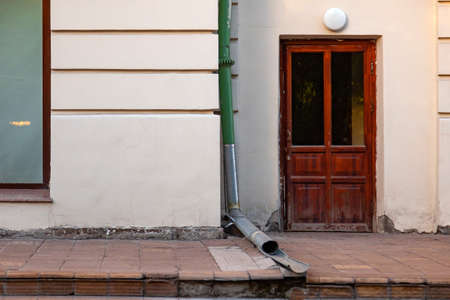 Close-up on the wall of an old building with a wooden brown door with a lamp for illuminating the entrance and a green drain pipe over gray paving slabs partially destroyed in Novosibirsk