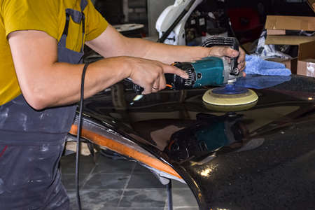 Close-up view on the hands of a male worker in yellow shirt who holds a tool for polishing the hood of a car while working in a vehicle detailing workshop.