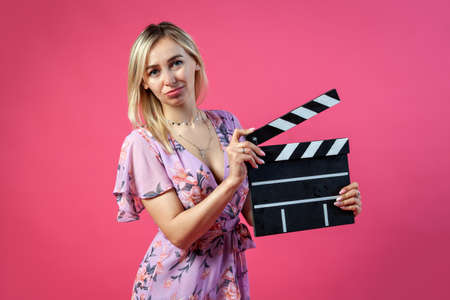 Beautiful blonde woman in a purple sundress holds an open clapperboard filmmaker in black with white stripes to start shooting a film on a pink isolated background