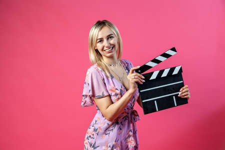 Beautiful blonde girl in a purple sundress holds an open clapperboard filmmaker in black with white stripes to start shooting a film on a pink isolated background