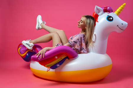 A beautiful woman blonde in a sexy sundress in white sneakers sits lifting her legs up on an inflatable multi-colored unicorn on a pink isolated background. Summer vacation at the beach and travel. Stock Photo