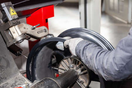 The process of repairing an automobile wheel using a special press on a machine for straightening disks for vehicles after damage in a pit on the road in the workshop by worker hands in gloves.