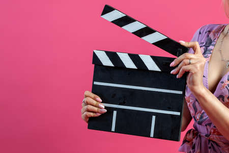 Arms of girl in a purple sundress holds an open clapperboard filmmaker in black with white stripes to start shooting a film on a pink isolated background. The concept of the beginning and start.