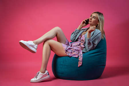 Beautiful blonde girl in a blue jacket and a purple sundress sits on a green bag chair with her legs folded on a pink isolated background and talking on the phone with a smartphone to her ear Stock Photo