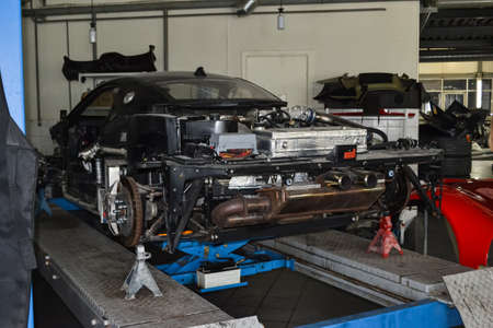 The frame of a powerful sports turbo car of red color with the removed body elements on the lift and the supports without wheels during the repair in the auto service station Stock Photo