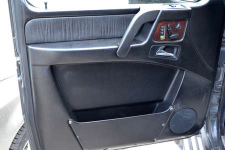 A close-up view of a part of the interior of a old classic car with a view of a black door with brown wood and leather trim after dry cleaning. Auto service industry.