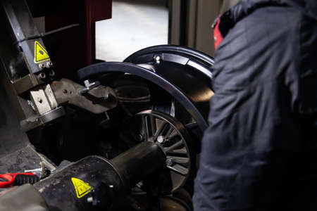 The process of repairing an automobile wheel using a special press on a machine for straightening disks for vehicles after damage in a pit on the road in the workshop. Auto service industry.