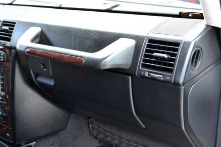 Close-up on the element of the interior of the car overlooking the glove box with a large black handle for the front passenger upholstered in black leather next to the duct Фото со стока