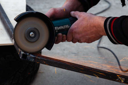 Close-up view strong man master without gloves on arms, performs metal cutting with an angle grinder in the garage workshop, blue and orange sparks fly to the sides. Safety breach in industry. Stock Photo