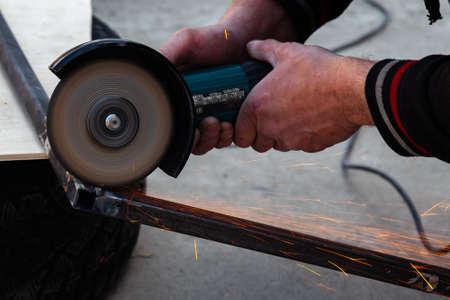Nahaufnahme eines starken Mannes ohne Handschuhe an den Armen, führt Metallschneiden mit einem Winkelschleifer in der Garagenwerkstatt durch, blaue und orange Funken fliegen zu den Seiten. Sicherheitsverletzung in der Industrie.
