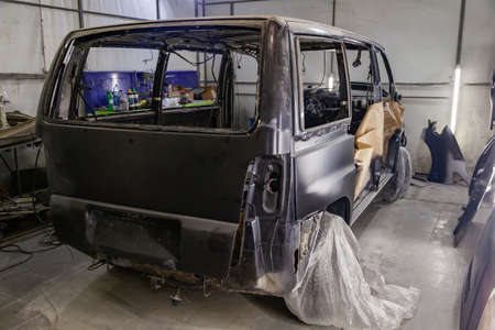 A large black matte car without windows is covered in paper and adhesive tape to protect against splash during painting and repair after an accident in a workshop for body repair of vehicles Фото со стока