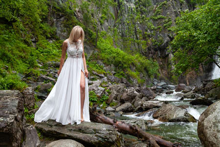 A young blond girl in an elegant pose bares her leg while reclining the hem of a boudoir dress, in the mountains against waterfall and stones, like a ballerina on a warm summer day in Altai green tree