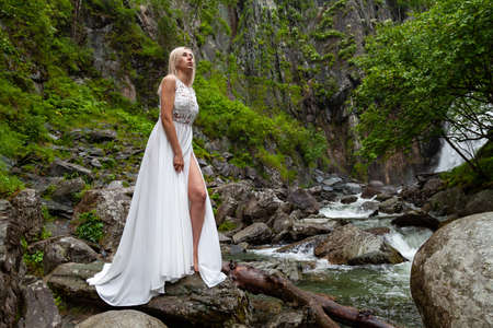 A young blond girl in an elegant pose bares her leg while reclining the hem of a boudoir dress, in the mountains against waterfall and stones, like a ballerina on a warm summer day in Altai green tree Reklamní fotografie