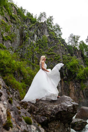 A young blonde girl in an elegant pose throws up hem of a boudoir dress in the mountains against a waterfall and stones raising her hands up like a ballerina on a warm summer day in Altai green trees