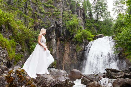 A young blonde girl in an elegant pose hold in arms hem of a boudoir dress in the mountains against a waterfall and stones looking back like a ballerina on a summer day in Altai green trees