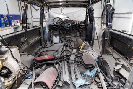 Car interior in the back of a van with a disassembled lining, seats removed, spare parts lying on the floor glass and rubber seal during preparation in a vehicle repair workshop. Auto service industry Stock Photo