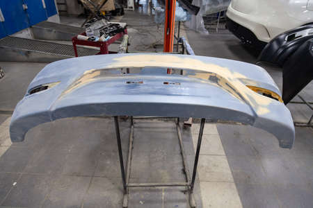 Repair of the rear bumper of a blue car after an accident with the help of multi-colored putty in a workshop for painting vehicles in a special chamber. Auto service industry and industrial. 写真素材