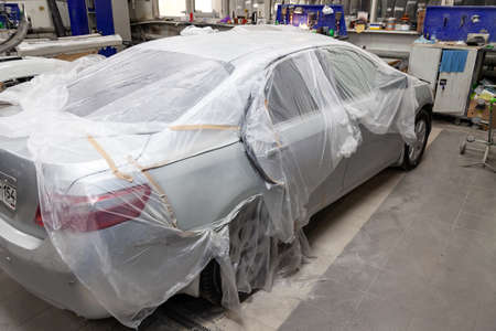 A broken car covered with a protective film from splashing paint in a spray booth in a car body repair shop before it is painted and repaired. Auto service industry.