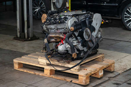 Replacement engine used on a pallet mounted for installation on a car after a breakdown and repair in a car repair workshop as a guarantee for the dealership. Auto service industry.