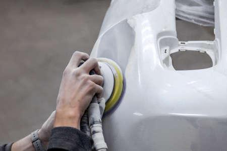 Preparación para pintar un elemento de automóvil con lijadora y masilla por parte de un técnico de servicio que nivela antes de aplicar una imprimación después de daños en una parte de la carrocería en un accidente en el taller del vehículo. Foto de archivo