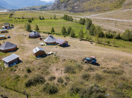 Aerial view of a settlement in the Altai Mountains with small houses for indigenous people and tourists, ail for nomadic living with green grass and trees. Traveling in deserted places. Stock fotó